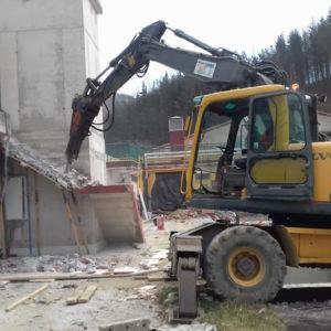 Retro excavadora con martillo neumático en la demolición de polideportivo